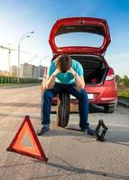 ledsen man sitter på reservhjulet nära trasig bil