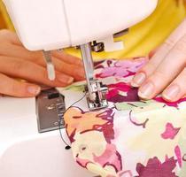 kvinnans sömmerska arbetar på symaskinen foto
