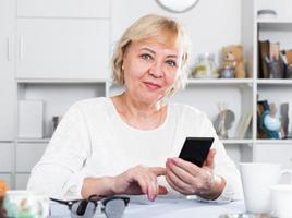 mogen kvinna med smartphone foto