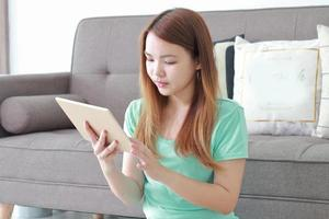ung kvinna som använder tabletten hemma. foto