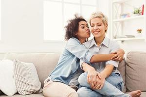 ung kvinna som kysser sin vän på kinden foto