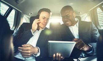 två kollegor som arbetar tillsammans i baksätet i en bil foto