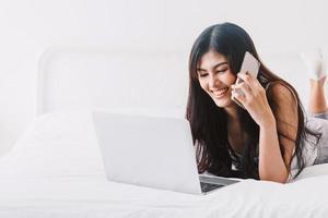 kvinna som använder digital labtopdator i sovrummet foto