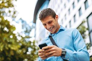 ung affärsman online via smartphone i staden foto