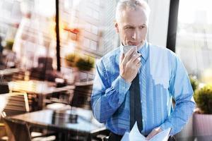 mogen affärsman som står med sin smartphone och ser fundersam foto