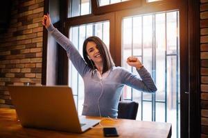 ung flicka sitter på café framför bärbar dator som lyfter upp sina händer. flicka tittar förvånansvärt på skärmen. tjejen är glad för att hon fick ett e-postmeddelande med goda nyheter. foto