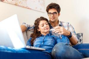 leende unga par som shoppar online via den bärbara datorn i deras hem. foto