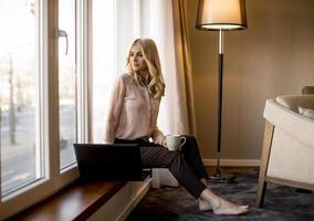 ganska ung kvinna med laptop och sitter vid fönstret foto