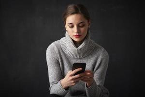 attraktiv ung kvinna med sin mobiltelefon foto