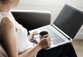 vit kvinna med laptop på soffan foto