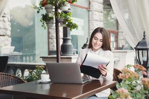ung affärskvinna som arbetar med papper utomhus foto