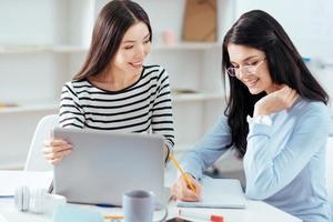glada kvinnliga kollegor noterar idéer foto