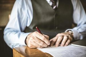 närbild av senior affärsman logga in papper. foto