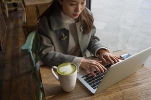 kvinna med matchakaffe med bärbar dator foto