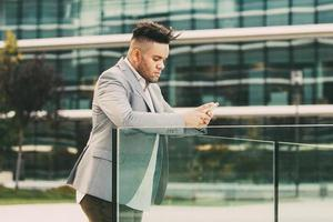 allvarlig manlig chef som antecknar på smarttelefonen foto