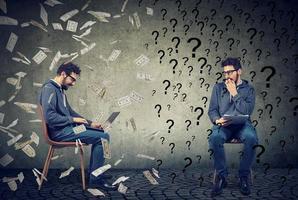 orolig man med frågor som tittar på framgångsrik smart kille som arbetar på bärbar dator under pengarregn foto