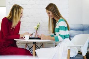 glada unga kvinnliga bästa vänner som använder moderna prylar för att dela multimediefiler medan de pratar med varandra och har kul, kvinnor synkroniserar mobiltelefon via Bluetooth-anslutning på kaffepaus foto