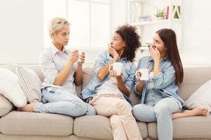 tre unga kvinnliga vänner med kaffe som pratar hemma foto