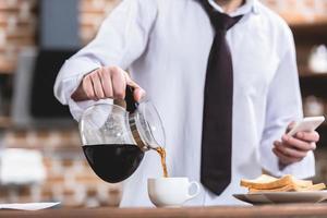 beskuren bild av ensam affärsman som häller kaffe och håller smarttelefonen i köket foto