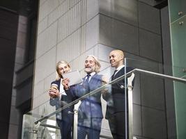 tre företagsledare som diskuterar affärer med digital tablet foto
