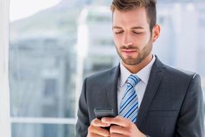 stilig ung affärsman textmeddelanden foto