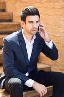 ung affärsman som pratar i mobiltelefon foto