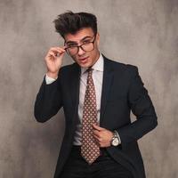 ung affärsman som tar av sig sina glasögon foto
