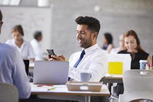 affärsman som skickar textmeddelande i mobiltelefon i office foto