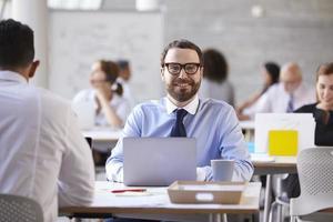 porträtt av affärsman som arbetar på bärbar dator på upptagen kontor foto