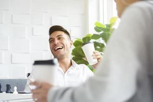 en man i avslappnad vit skjorta skrattar och dricker kaffe medan han möter sina kollegor i det grönska vita kontorsskafferiet. foto