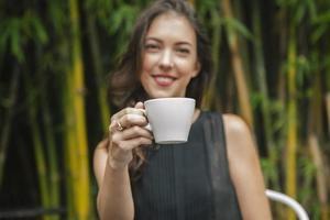 kvinna som håller en kopp varmt kaffe foto