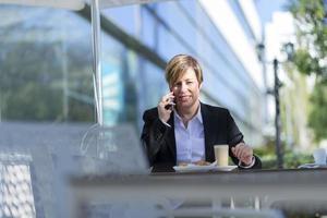 porträtt av en affärskvinna sitter avslappnad på utomhus kafé foto