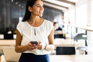 Håller kontakten. ung affärskvinna i formalwear som håller mobiltelefon medan hon sitter på sin arbetsplats foto