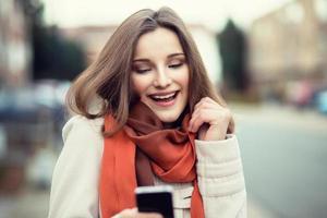 kvinna sms. närbild ung glad le gladlynt vacker kvinna flicka tittar på mobiltelefon läsning skicka sms isolerade stadsbild utomhus bakgrund. positivt ansiktsuttryck mänskliga känslor. multikulturell, blandras, asiatisk rysk modell foto