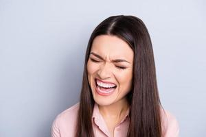 porträtt av psyko, nervös, gråtande, okontrollerbar kvinna med våldsam irriterad reaktion, ropade med nära ögon, grimas, trött från rutin isolerad på grå bakgrund foto