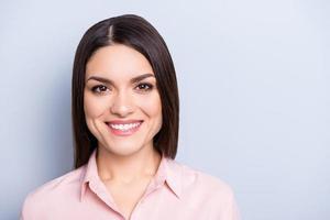 porträtt med kopia utrymme tom plats för vacker, charmig, vacker, trevlig, leende kvinna i klassisk skjorta isolerad på grå bakgrund tittar på kameran foto