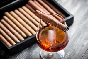 brinnande cigarr på glas med cognac foto