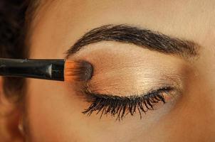 kvinna applicera makeup ögonskugga foto