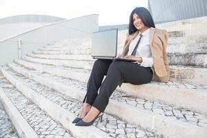 glad latinamerikansk kvinnlig chef njuter av frilansarbete foto
