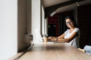 söker efter ny lösning. fundersam ung vacker affärskvinna i glasögon som arbetar på bärbar dator medan hon sitter på hennes arbetsplats foto