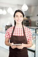 ung servitris poserar i café