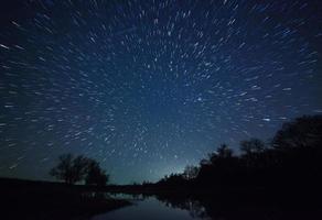 vacker natthimmel, mjölkvägen, stjärnspår och träd foto