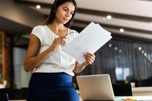 letar efter rätt dokument. vacker ung kvinna som undersöker dokument i office foto