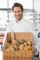 bagare visar korg med bröd foto