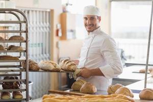 leende bagare innehav bricka med bröd foto