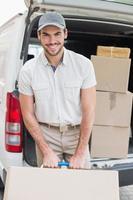 leveransförare som laddar sin skåpbil med lådor foto