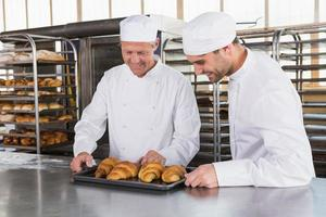leende bagare som ser brickor av croissanter foto