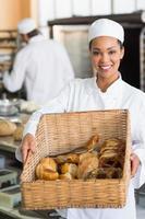 vacker bagare som visar korg med bröd foto