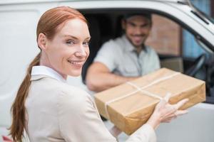 leveransförare som lämnar paketet till kunden i sin skåpbil