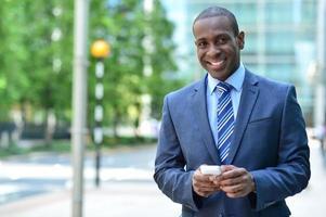 leende affärsman innehar smartphone foto